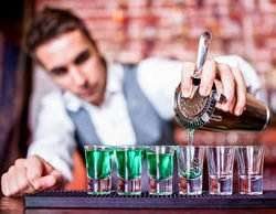 Nightclub Bartender pouring green shots