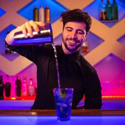 Bartender pouring drink purple background