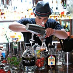 bartender with hat pouring a cocktail